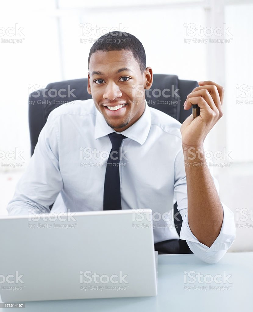 Businessman sitting in front of laptop and smiling royalty-free stock photo
