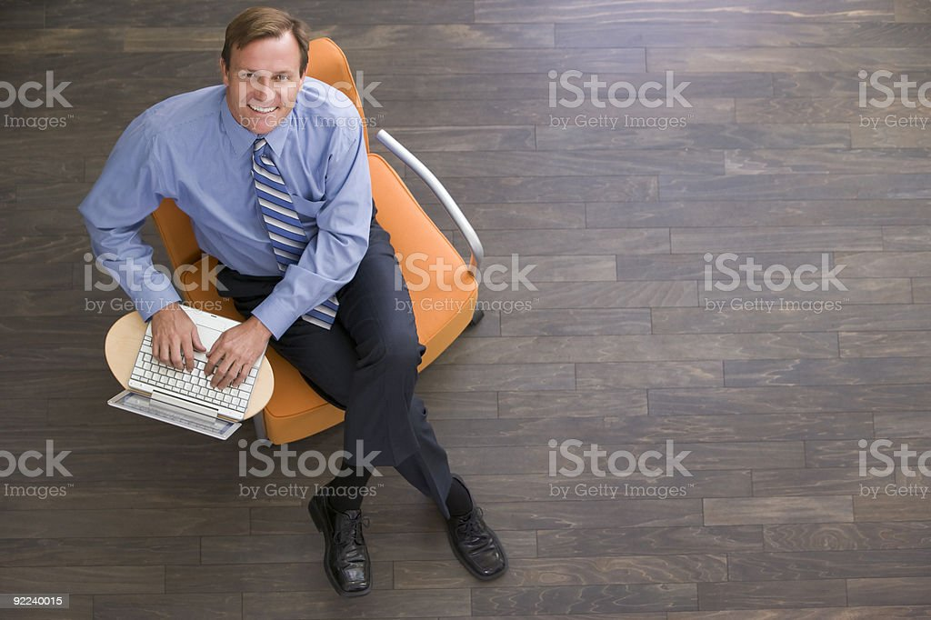 Businessman sitting indoors with laptop smiling royalty-free stock photo