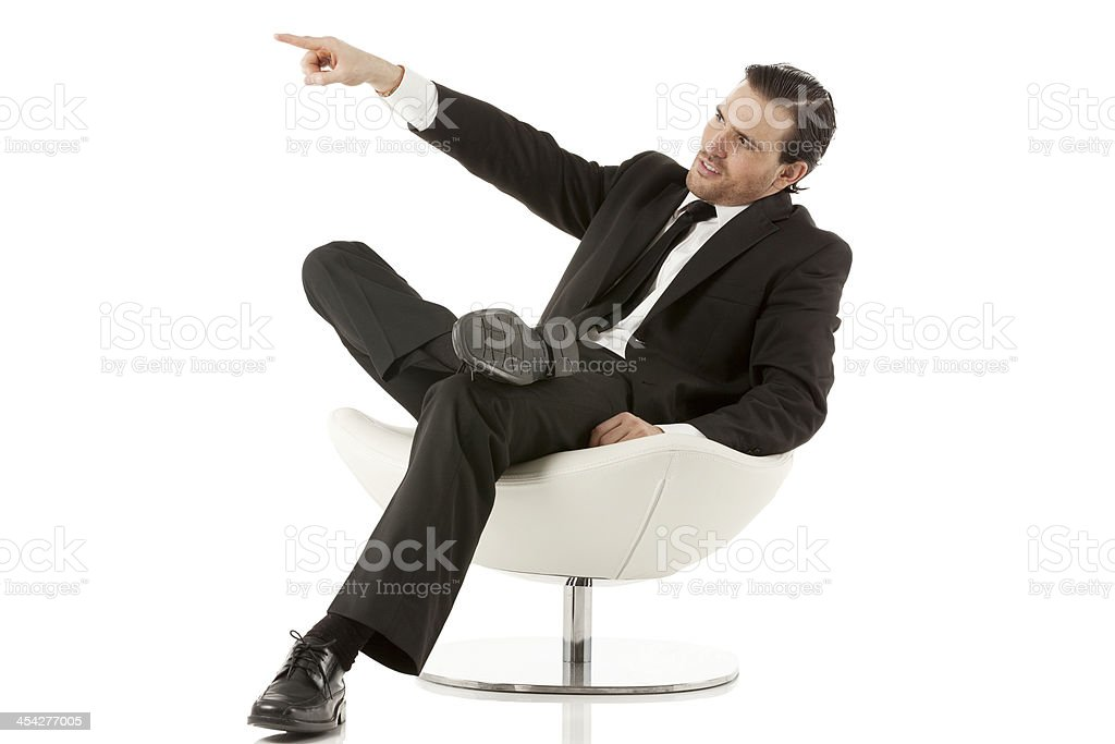 Businessman sitting on a chair and gesturing royalty-free stock photo