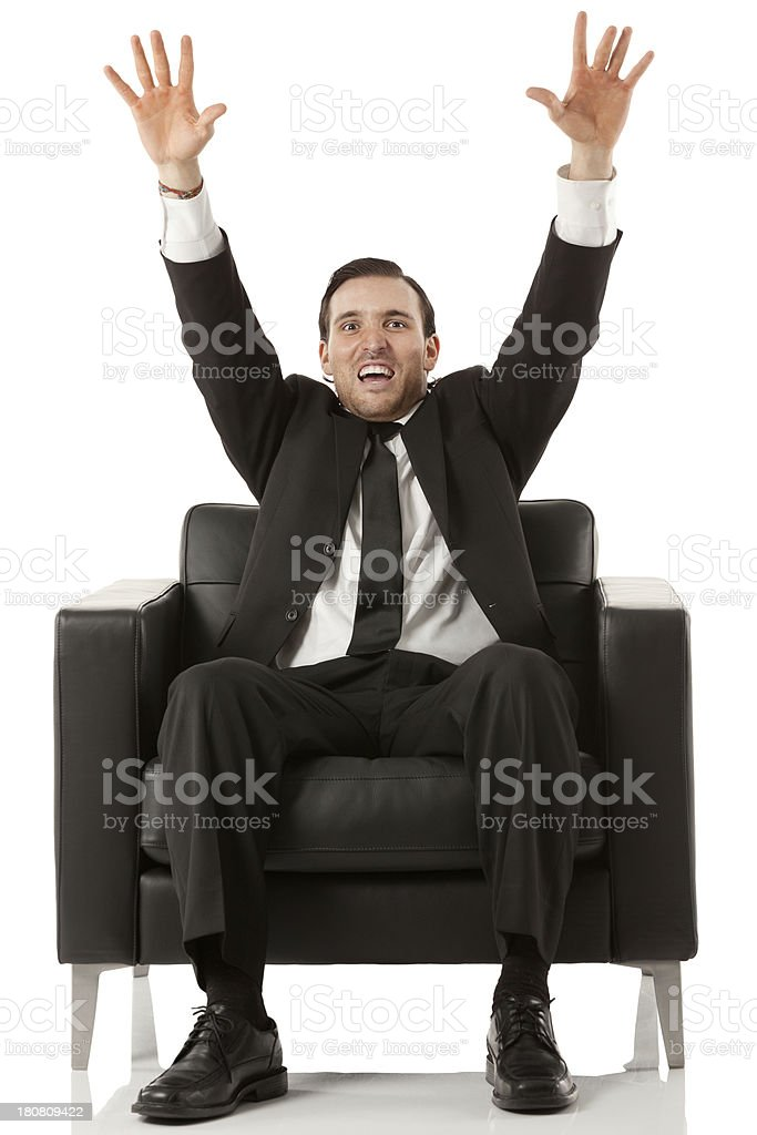 Businessman sitting on a couch with his arms raised royalty-free stock photo