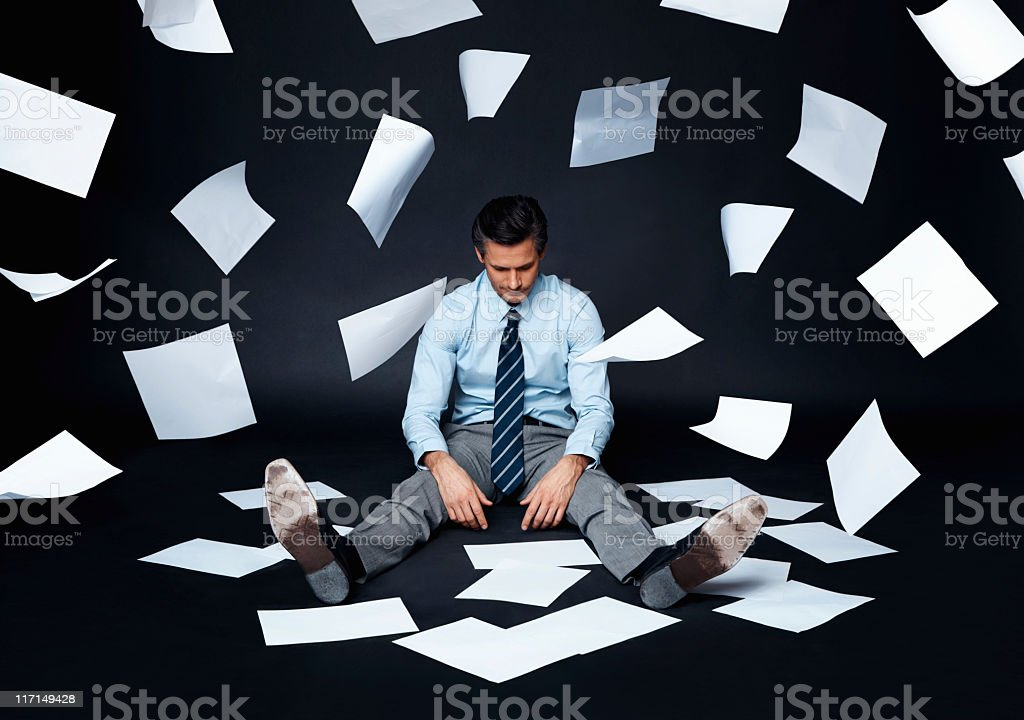 Businessman sitting on a dark surface with papers flying stock photo