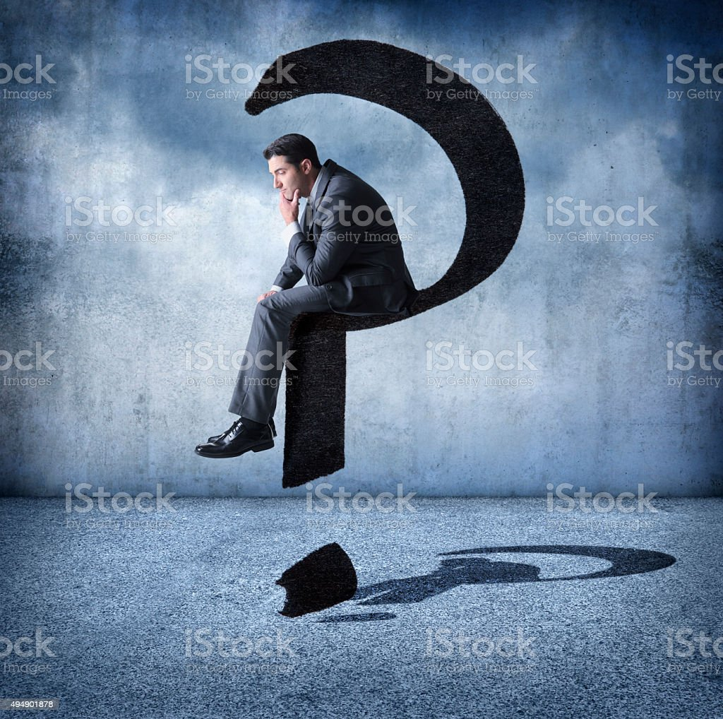 Businessman Sitting On A Floating Question Mark stock photo