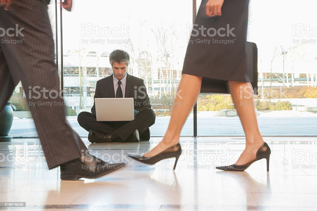 Businessman sitting on a floor in a busy hallway stock photo
