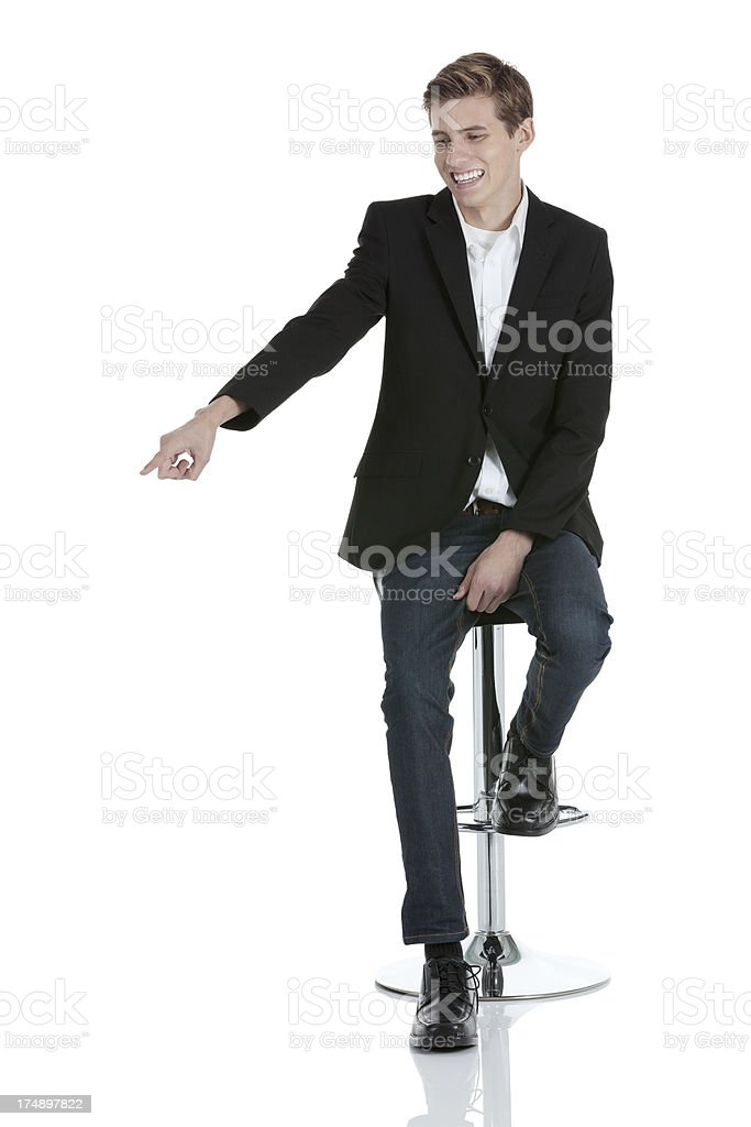 Businessman sitting on a stool pointing with finger royalty-free stock photo