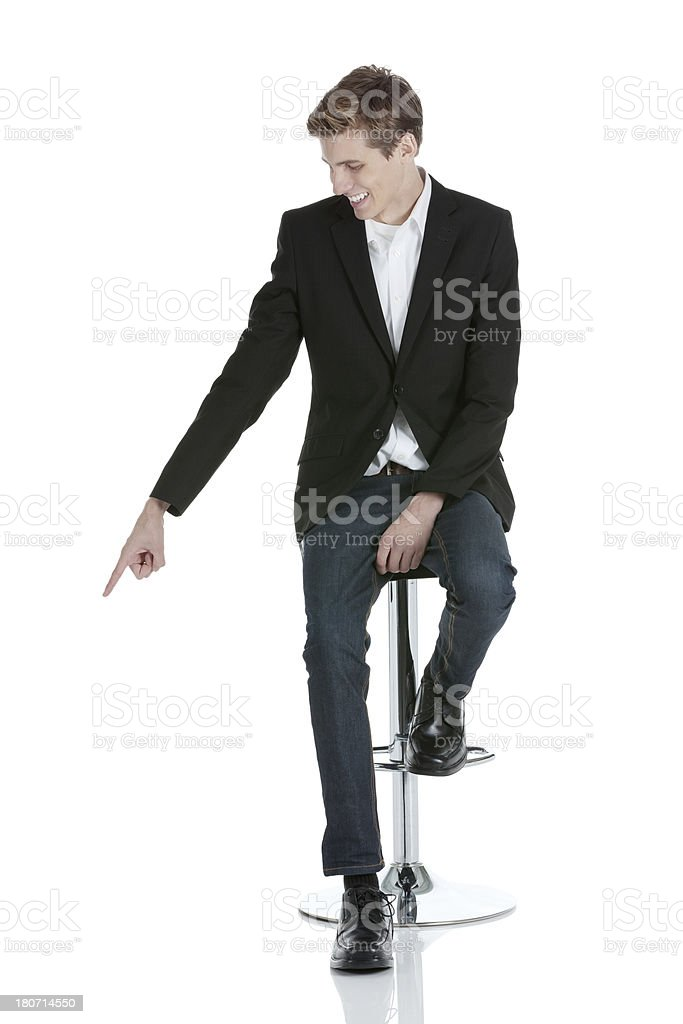 Businessman sitting on a stool pointing with finger stock photo