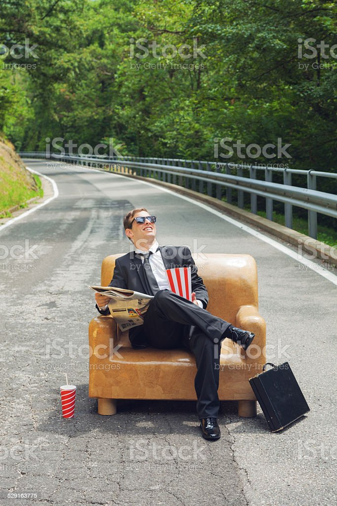 businessman sitting on armchair in middle of the road stock photo