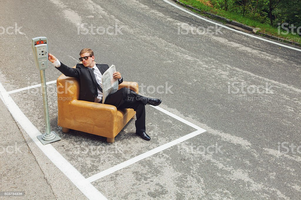 businessman sitting on armchair in the middle of the road stock photo