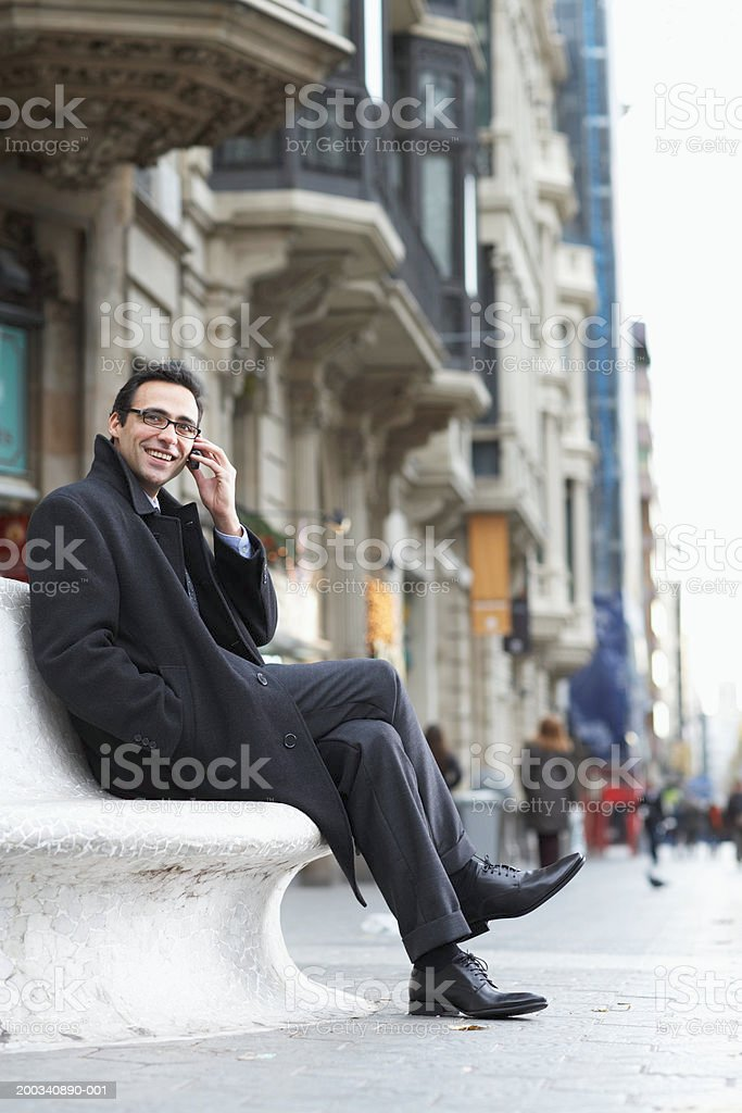 Businessman sitting on bench by street, using mobile phone, smiling royalty-free stock photo