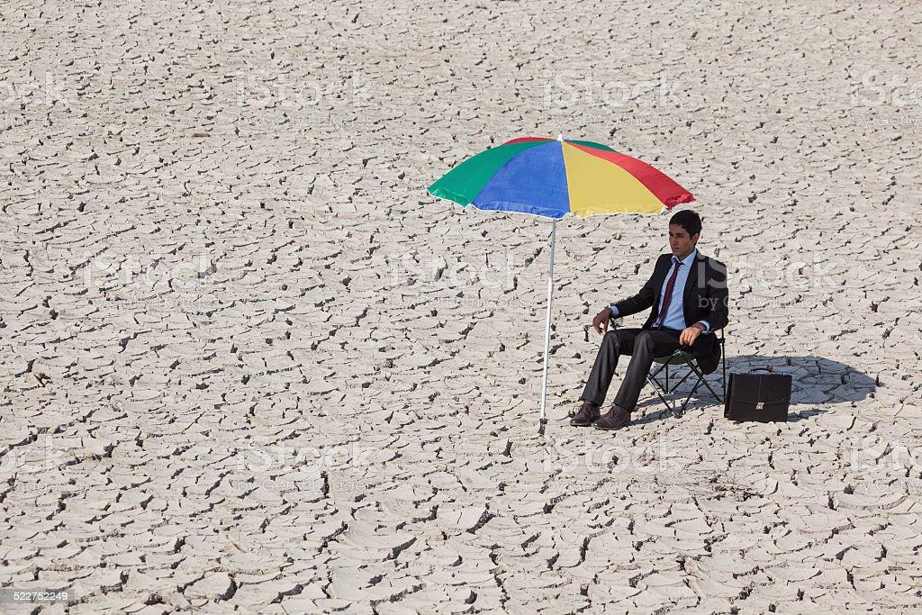 Businessman sitting on chair under parasol in desert stock photo