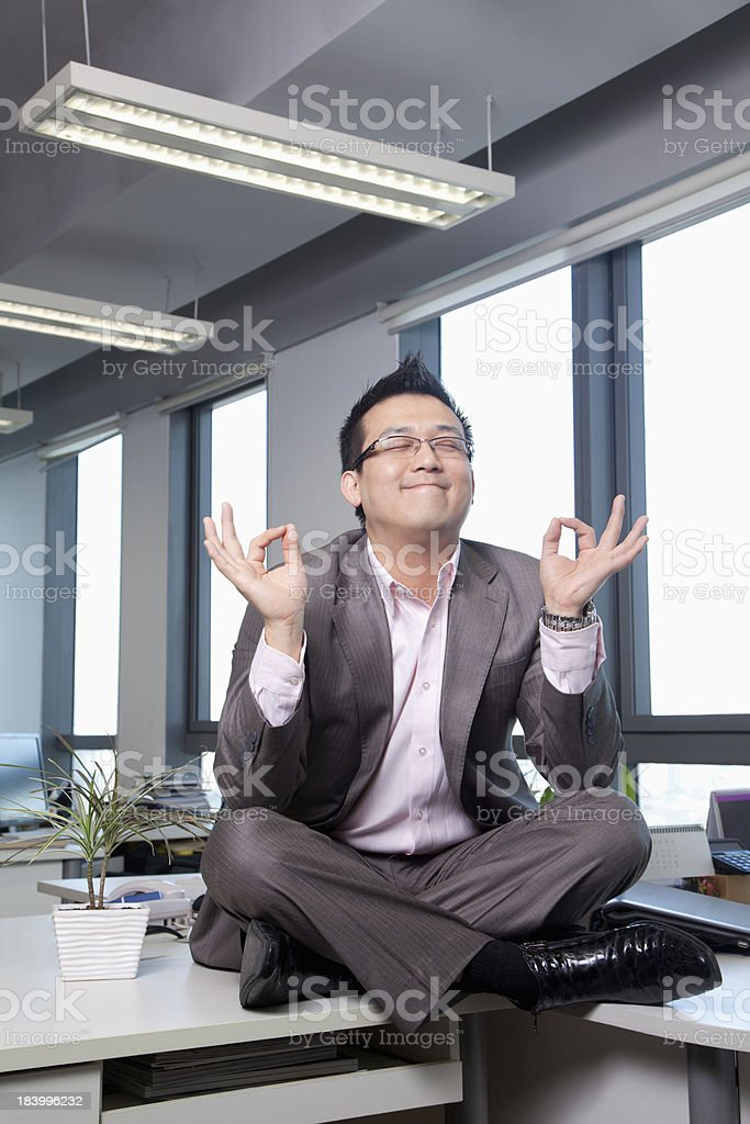 Businessman sitting on desk in the office meditating royalty-free stock photo
