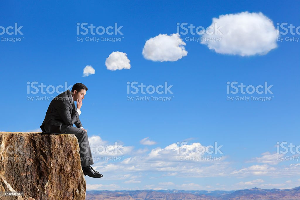 Businessman sitting on edge of cliff thinking stock photo