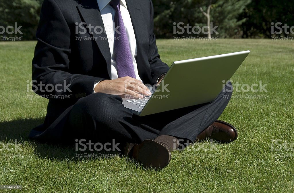 Businessman sitting on grass using laptop, Istanbul, Turkey royalty-free stock photo