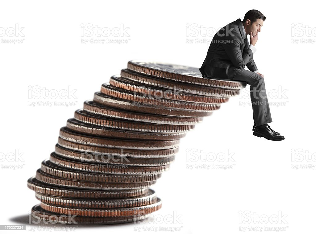 Businessman sitting on leaning stack of coins royalty-free stock photo