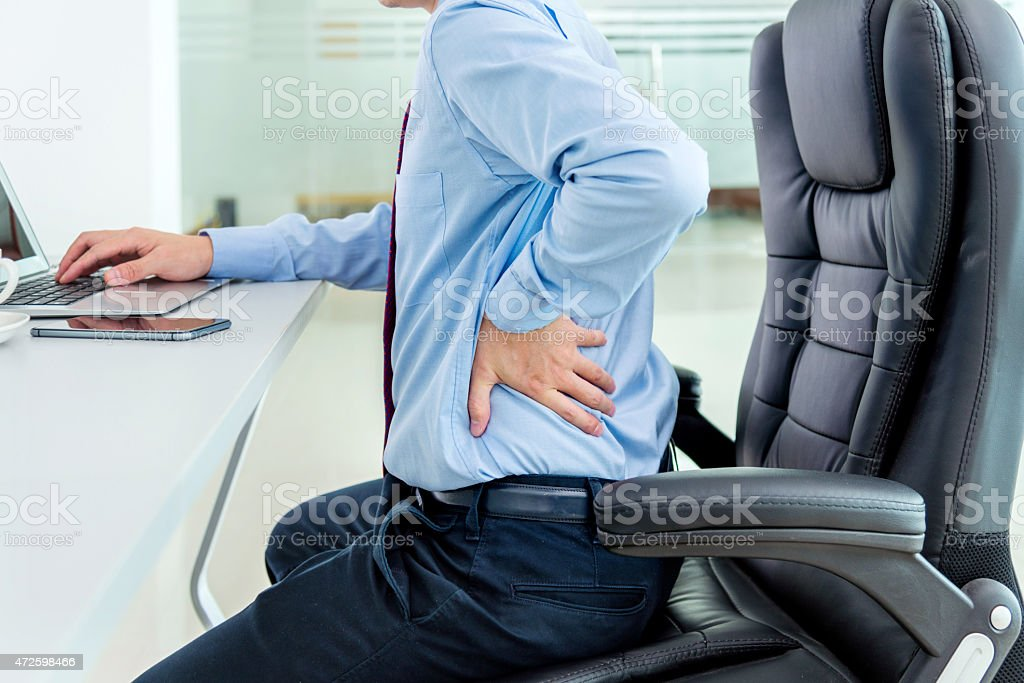 Businessman sitting on leather chair with hand on back stock photo