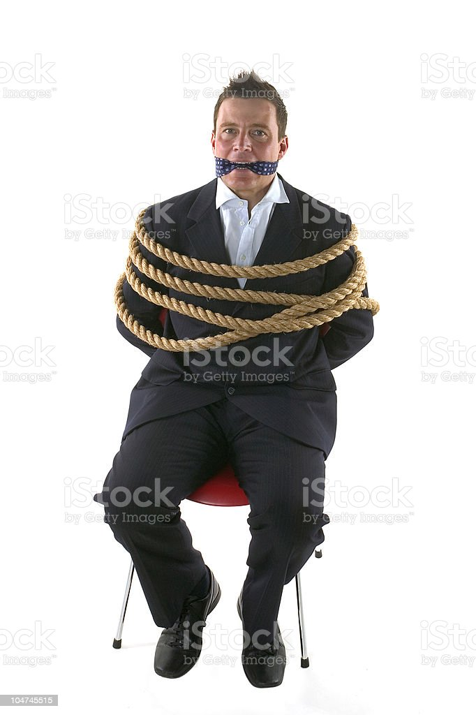 Businessman sitting on red chair with tie on mouth and ropes stock photo