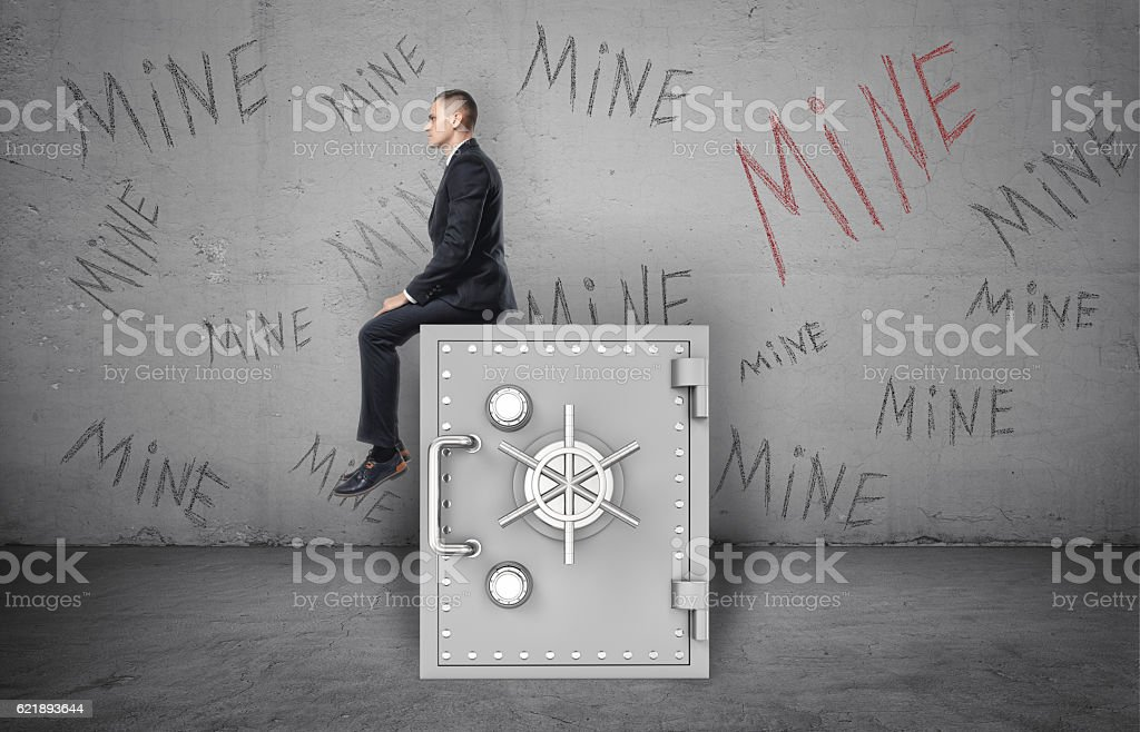Businessman sitting on safe and background of wall with inscription stock photo