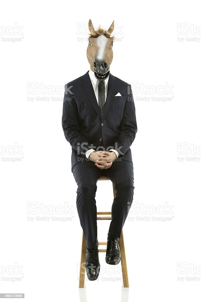 Businessman sitting on stool with horse head royalty-free stock photo
