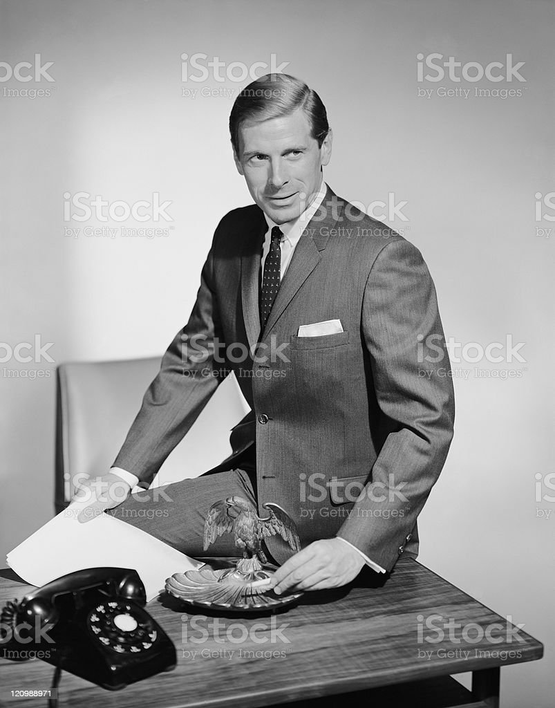 Businessman sitting on table near ash tray stock photo