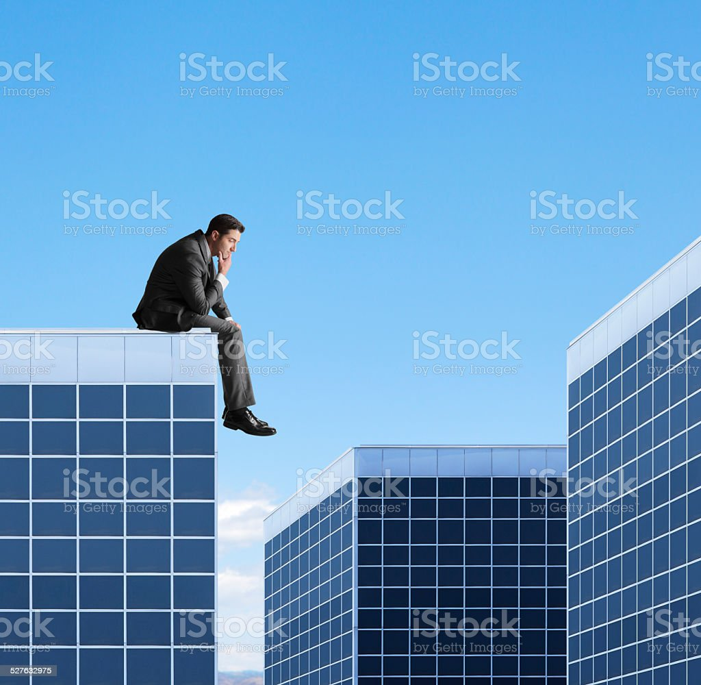 Businessman Sitting On Top Of Building stock photo