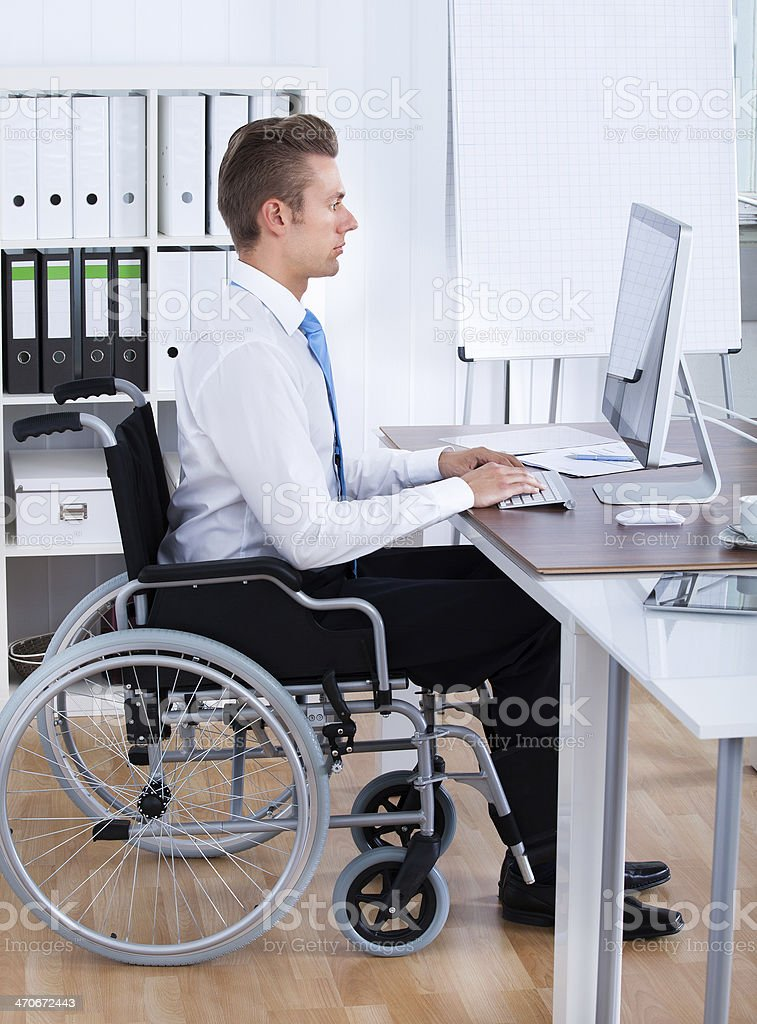 Businessman Sitting On Wheelchair And Using Computer royalty-free stock photo