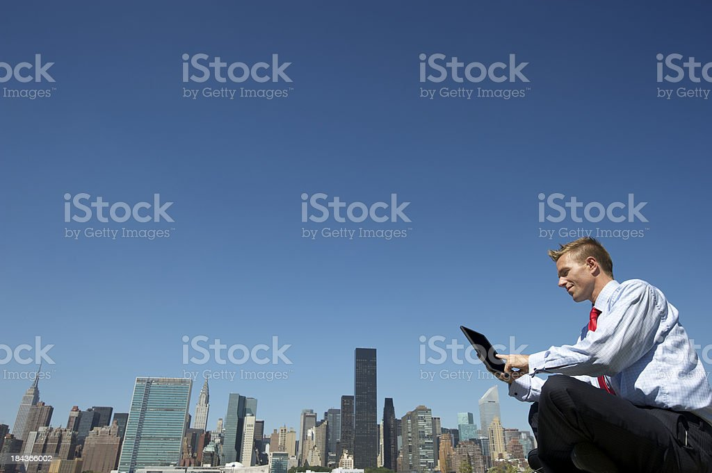 Businessman Sits Using Tablet Computer at City Skyline stock photo