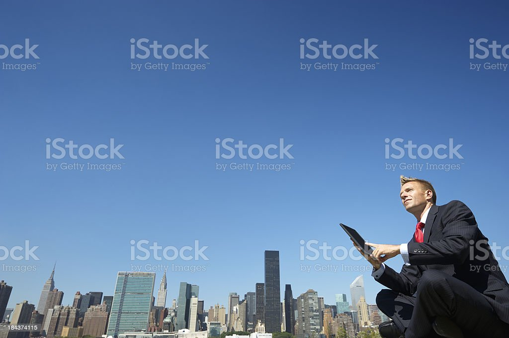 Businessman Sits Using Tablet Computer Outside City Skyline stock photo