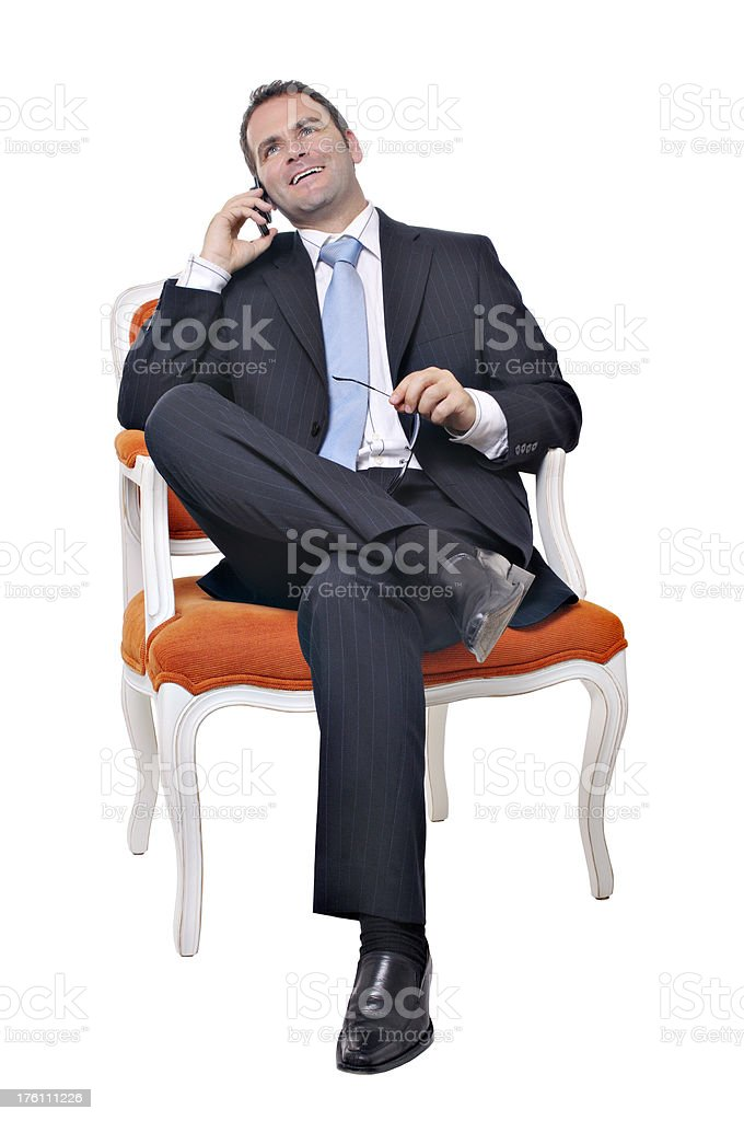 Businessman sitting while on the phone stock photo