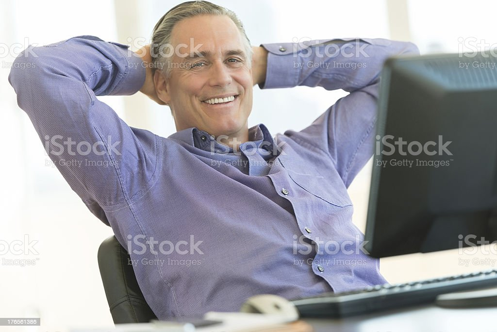 Businessman Sitting With Hands Behind Head At Office Desk stock photo