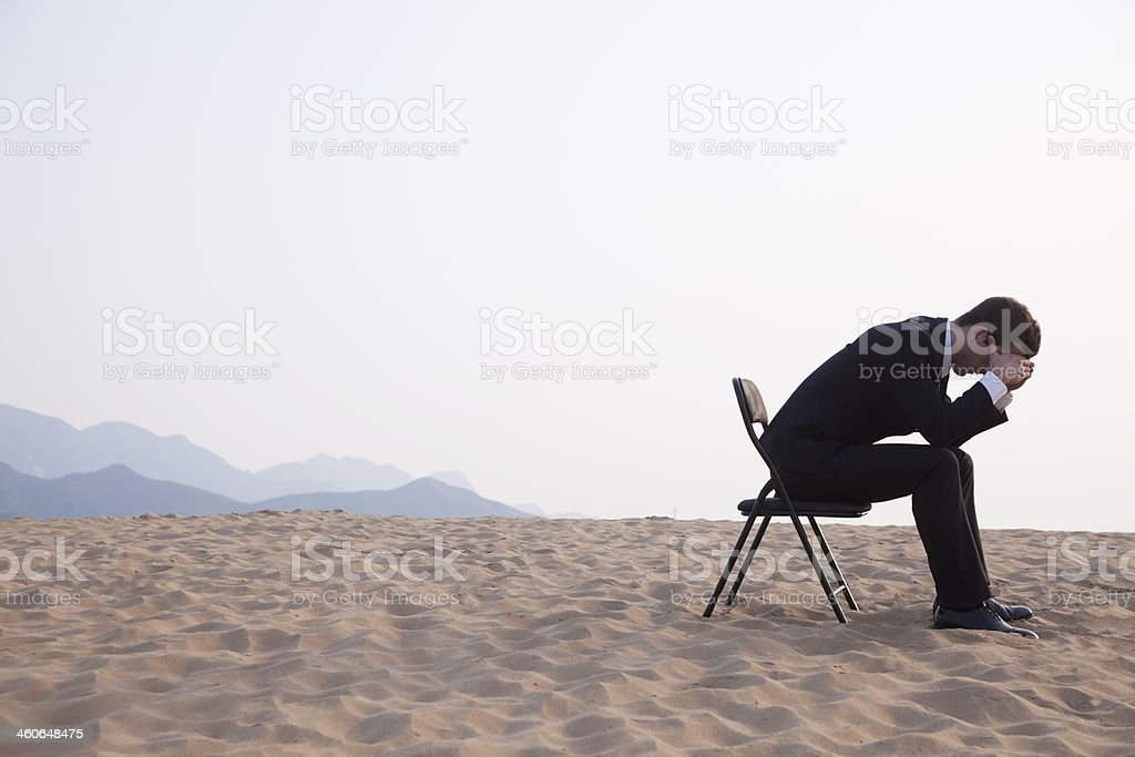 Businessman sitting with head in his hands stock photo
