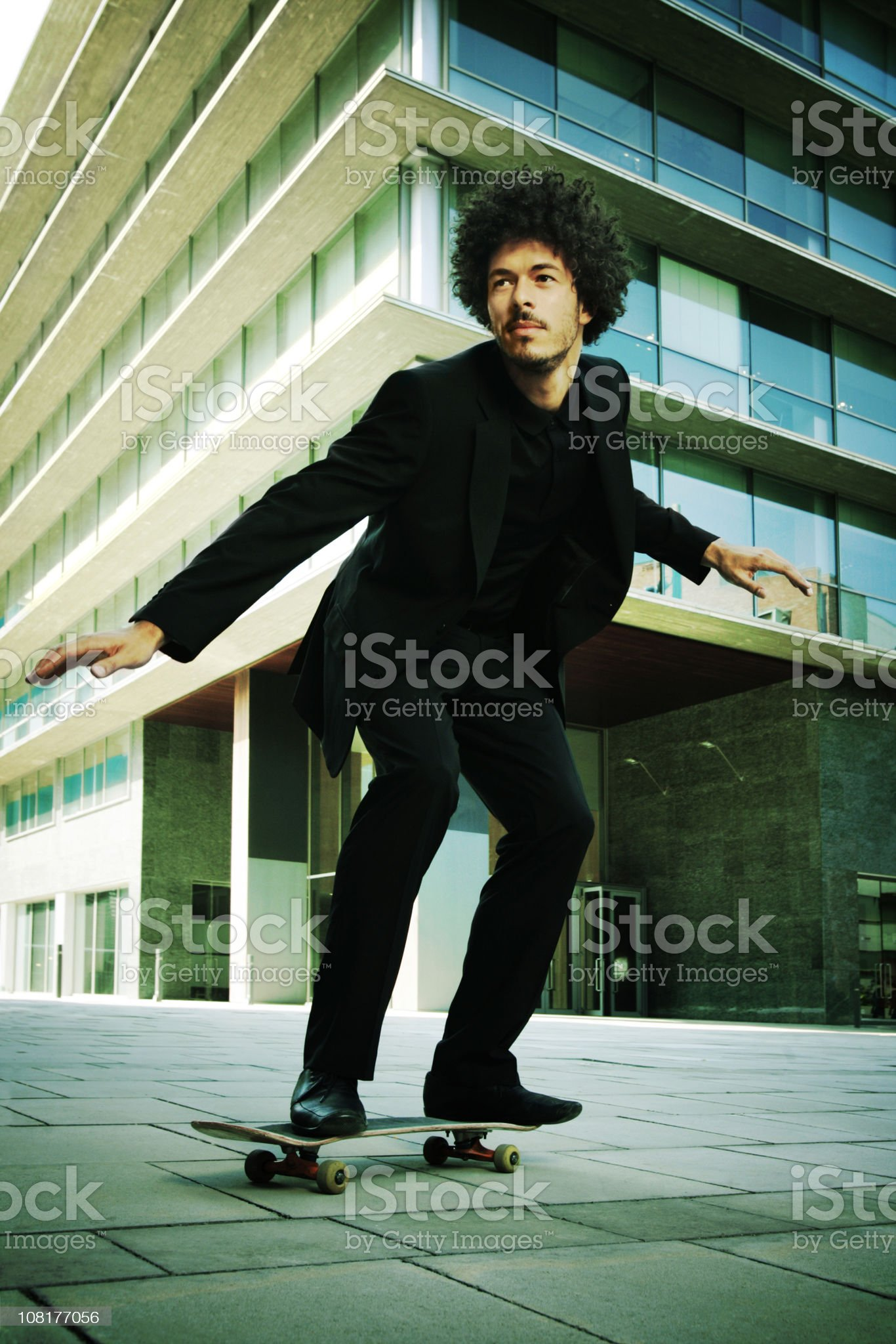 Businessman Skateboarding In Front of Office Building royalty-free stock photo