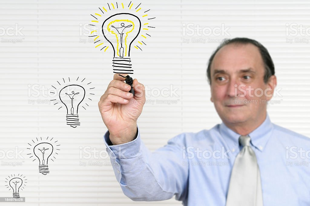 Businessman Sketching a Light Bulb royalty-free stock photo
