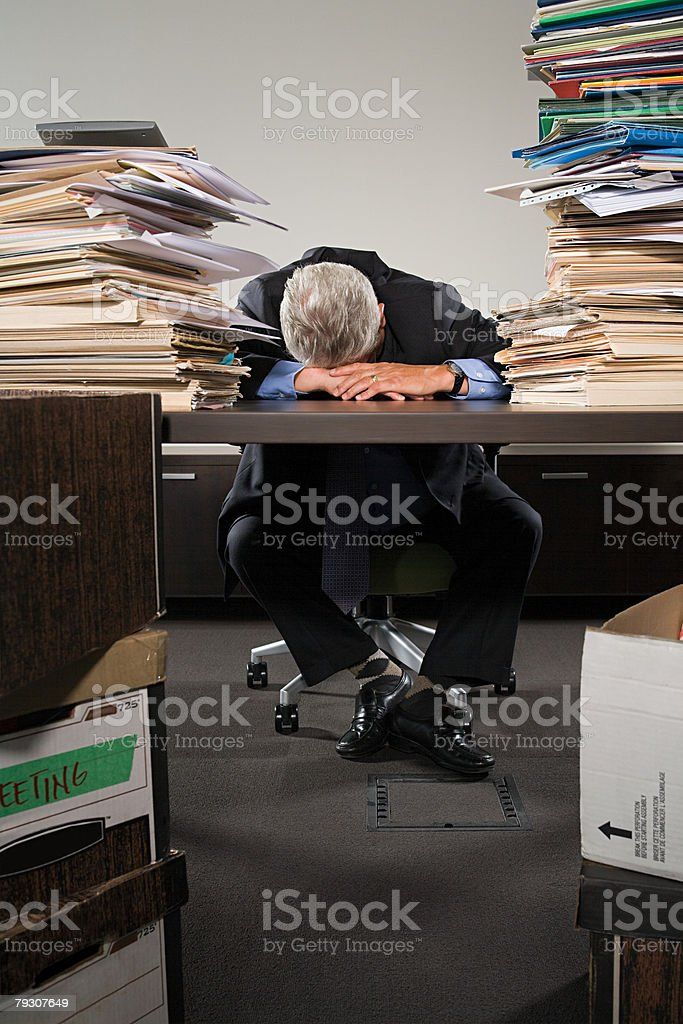 A businessman sleeping at his desk royalty-free stock photo
