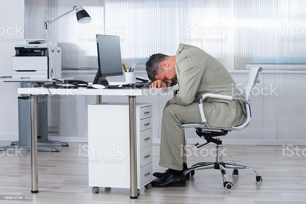 Businessman Sleeping On Desk In Office stock photo