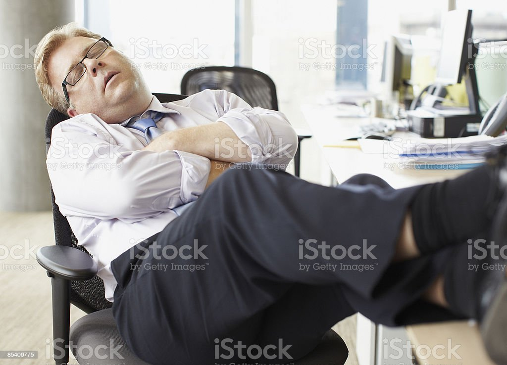 Businessman sleeping with feet up at desk stock photo