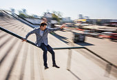 Businessman sliding down the rail in blurred motion.