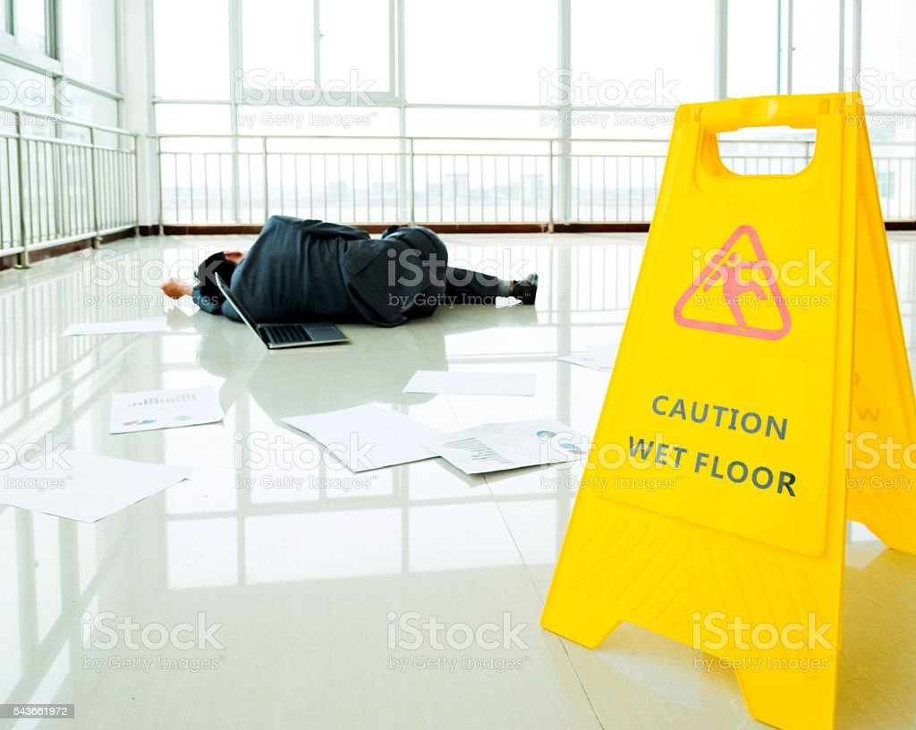Businessman slipped on a floor next to caution sign stock photo