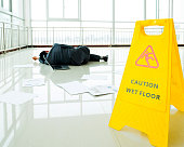 Businessman slipped on a floor next to caution sign