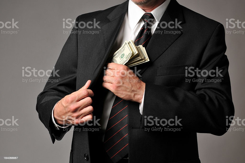 Businessman Slipping a Stack of Cash into His Suit Pocket royalty-free stock photo