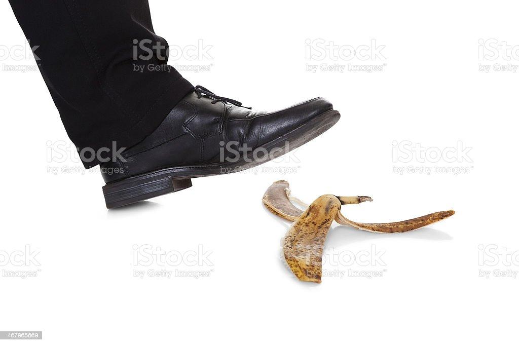 Businessman slipping on banana peel stock photo