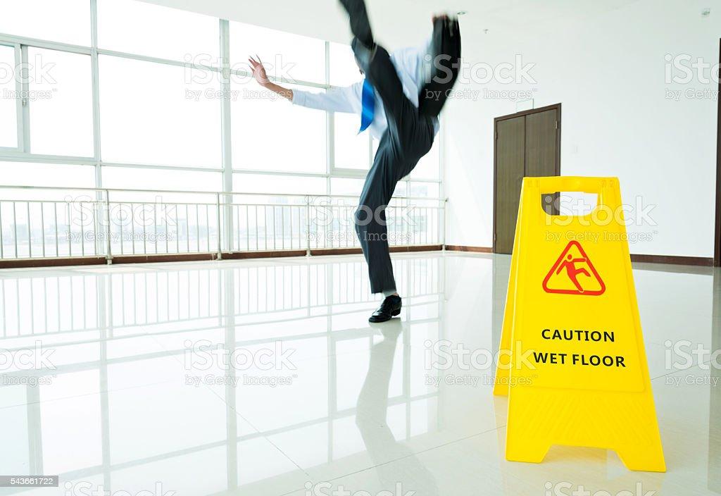 Businessman slipping on wet floor stock photo