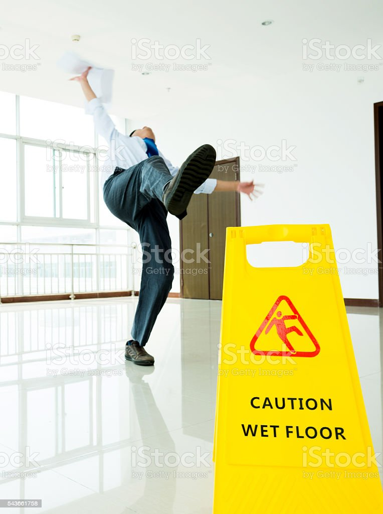 Businessman slipping on wet floor stock photo
