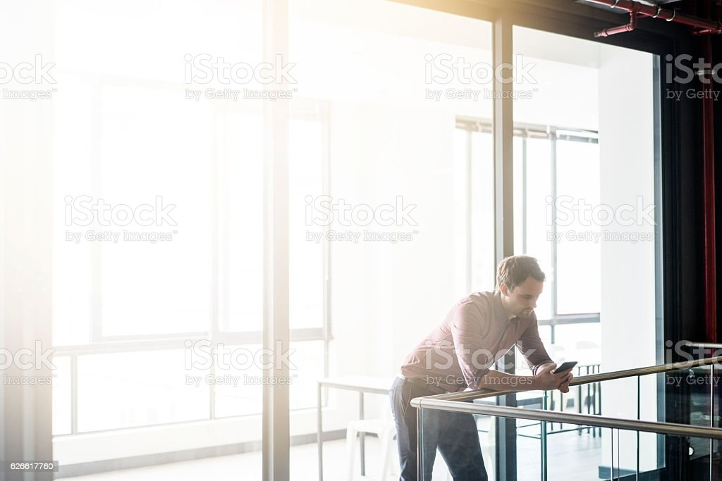 Businessman smart phone in brightly lit office stock photo