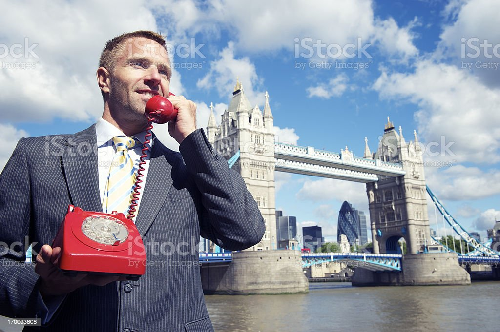 Businessman Smiles by Tower Bridge London Talking on Phone royalty-free stock photo