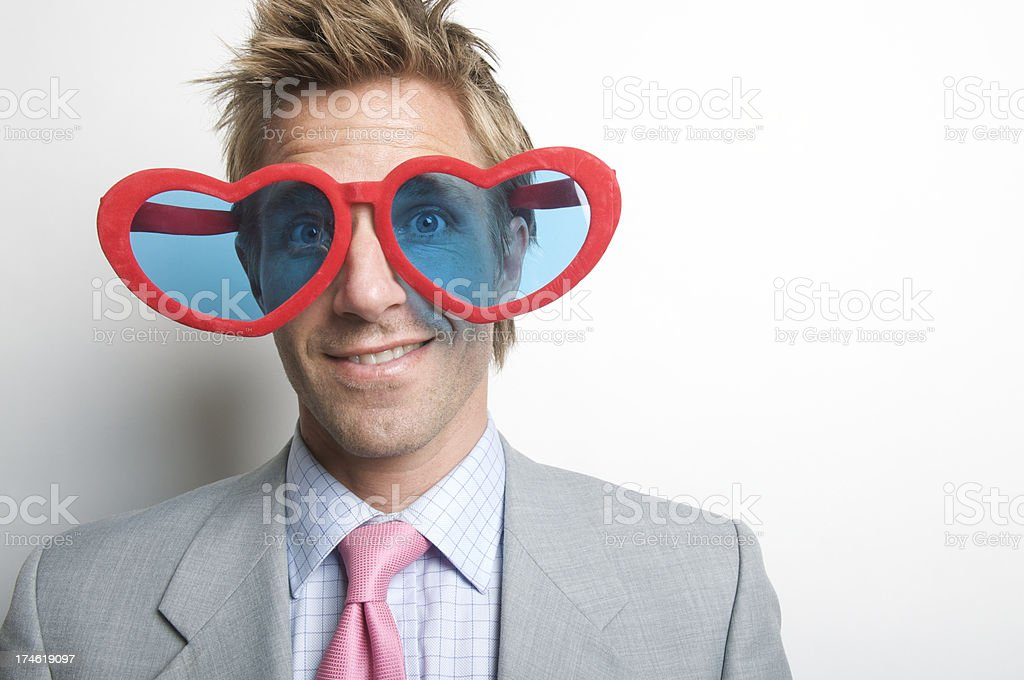 Businessman Smiles Wearing Red Heart Glasses White Wall stock photo