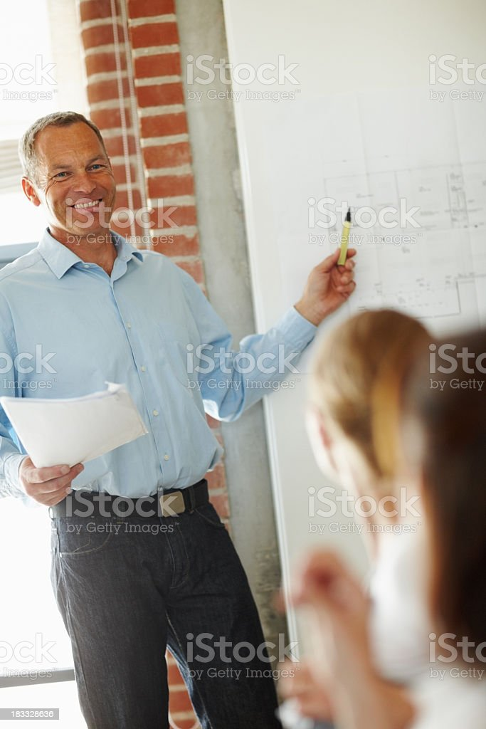 Businessman smiling during a presentation with colleagues royalty-free stock photo