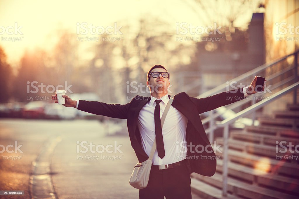 Businessman smiling with arms outstretched stock photo