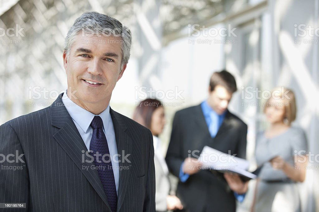 Businessman Smiling With Colleagues In Background stock photo