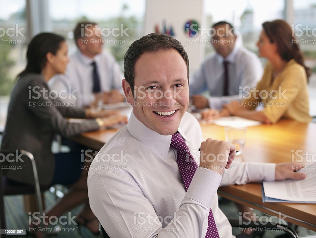 Businessman smiling with colleagues in discussion at the boardroom royalty-free stock photo