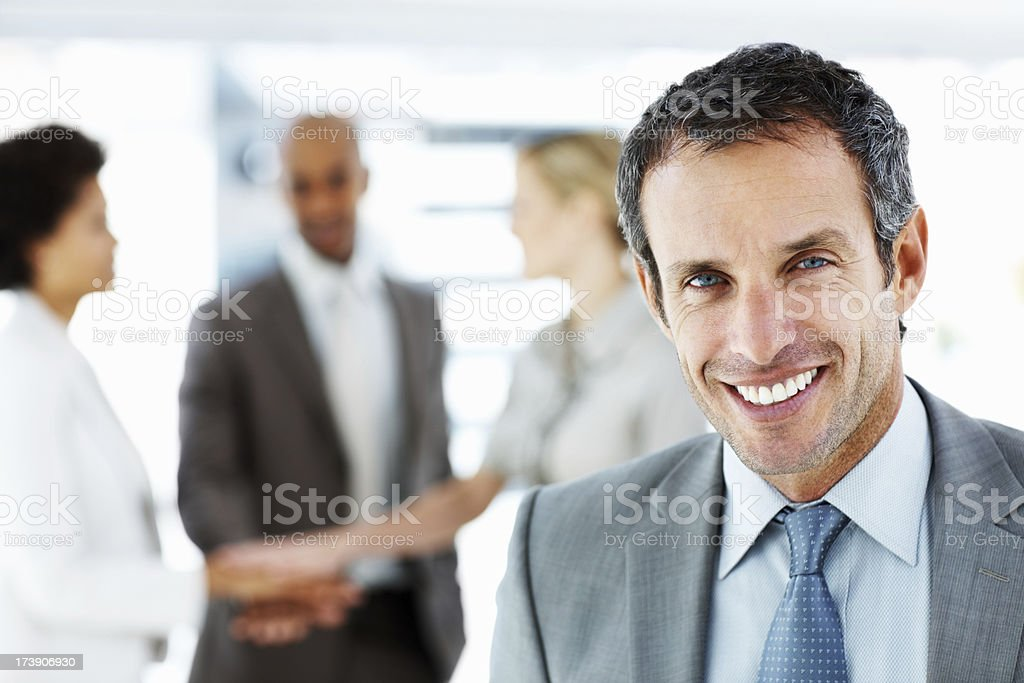 Businessman smiling with colleagues in the background royalty-free stock photo