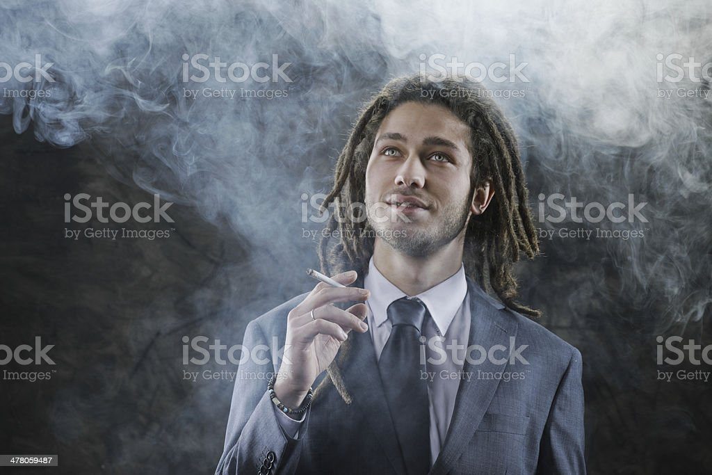 Businessman smoking a joint royalty-free stock photo